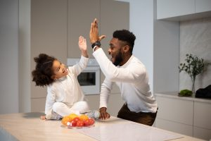 Father high diving a daughter who is sitting on a kitchen counter