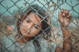 A young girl with a thoughtful expression behind a chain link fence with a minimal amount of tall grass growing on it