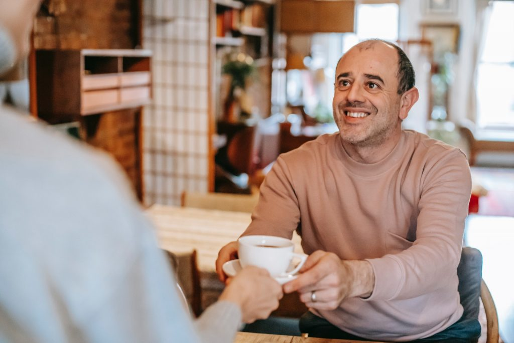 Man with an uncomfortable grin being given a cup of coffee